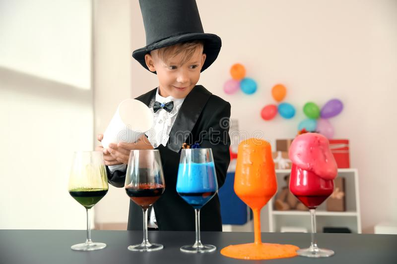 Cute little magician showing trick indoors stock photography