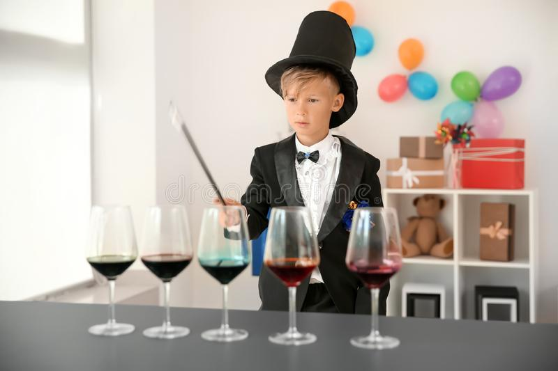 Cute little magician showing trick indoors royalty free stock image