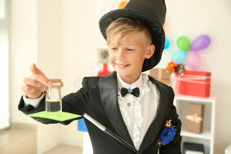 Cute little magician showing trick indoors royalty free stock photo