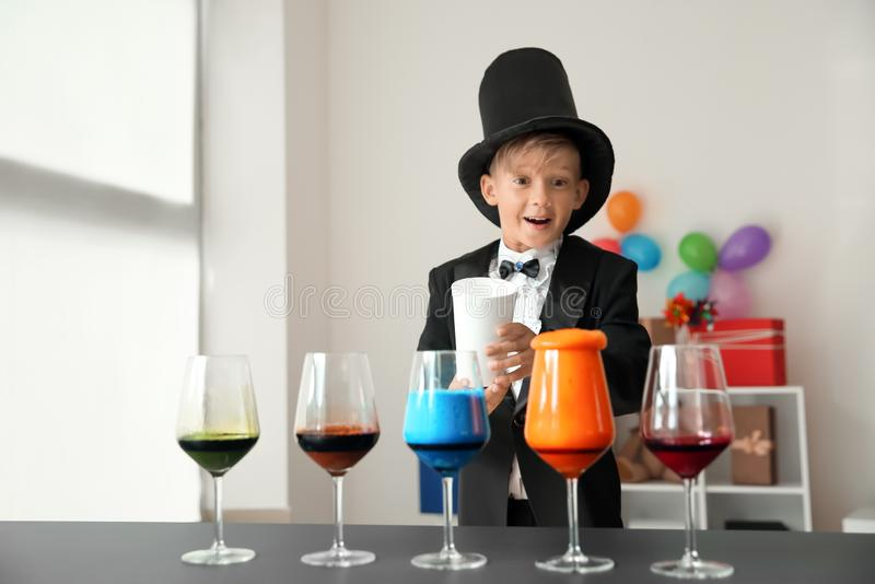 Cute little magician showing trick indoors stock photos