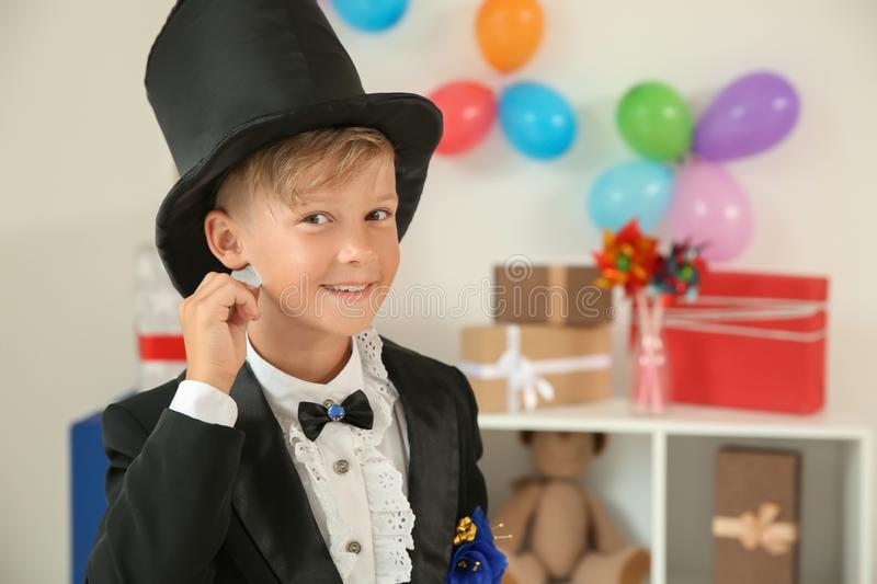 Cute little magician showing trick indoors stock photo