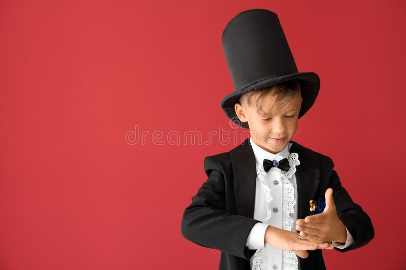 Cute little magician showing tricks on color background royalty free stock images