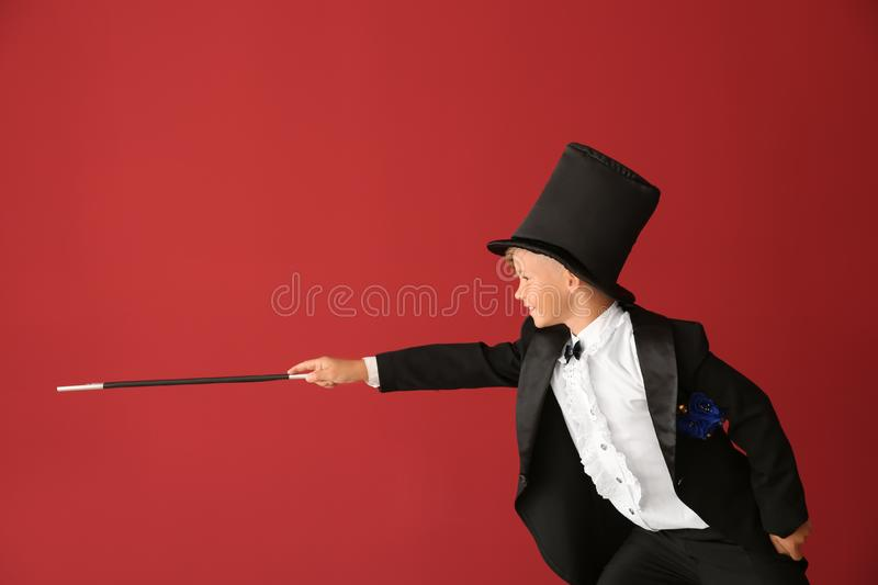 Cute little magician showing tricks on color background royalty free stock photo