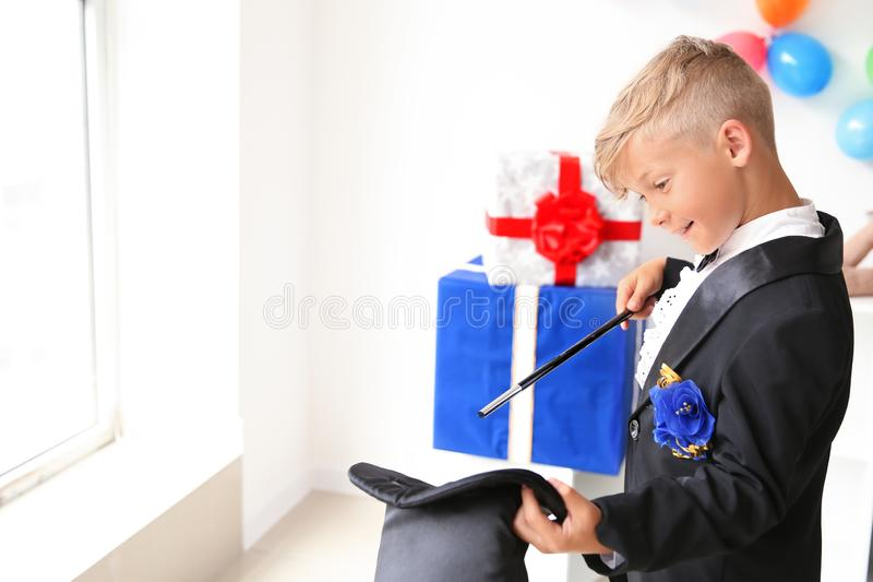 Cute little magician showing tricks with hat indoors stock photo
