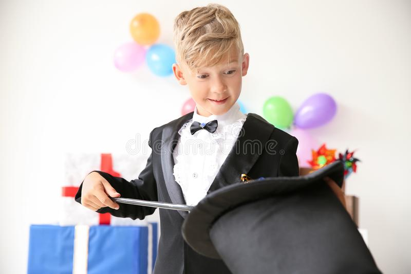 Cute little magician showing tricks with hat indoors royalty free stock photography
