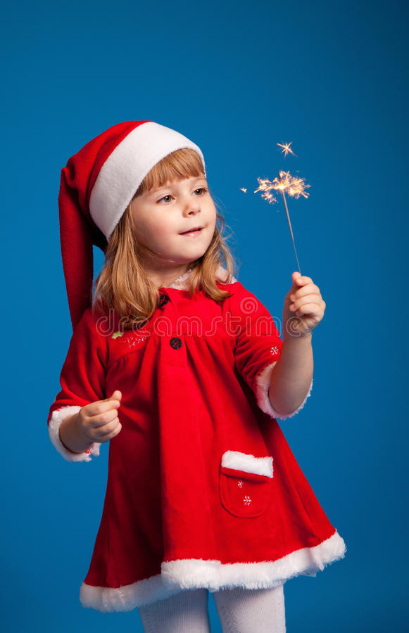 Cute little miss santa playing with Bengal fire stock image
