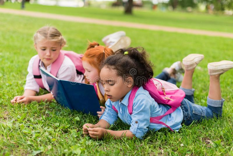 Multiethnic kids reading book on grass royalty free stock image