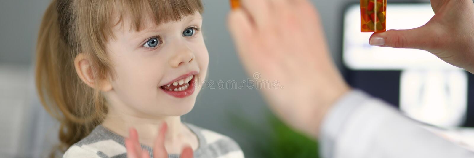 Cute little patient girl having fun selecting a bottle of medications royalty free stock image