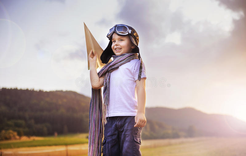 Cute little pilot holding a toy plane stock photography
