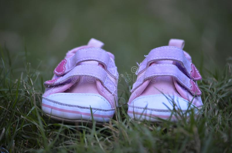 Cute Little Pink Shoes Relaxing on Green Grass. Cute baby pink shoes with green background royalty free stock photography