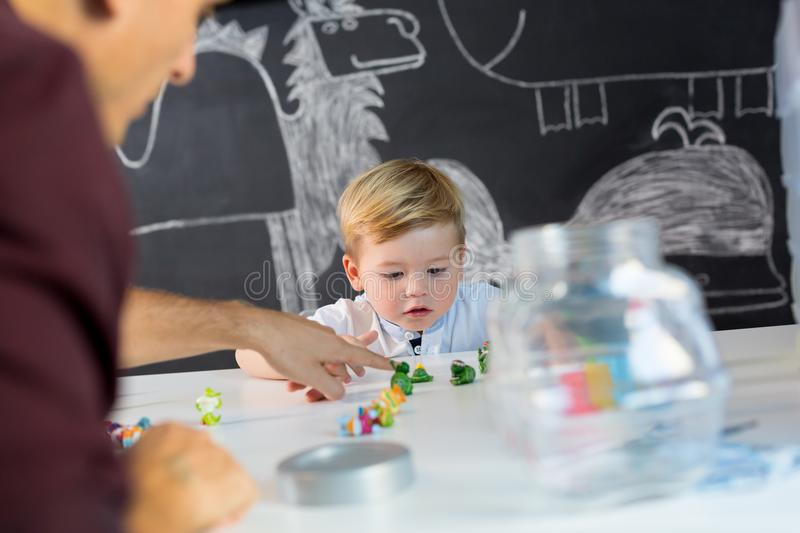 Cute little toddler boy at child therapy session. Cute little playfull toddler boy at child therapy session. Private one on one homeschooling with didactic aids royalty free stock photography