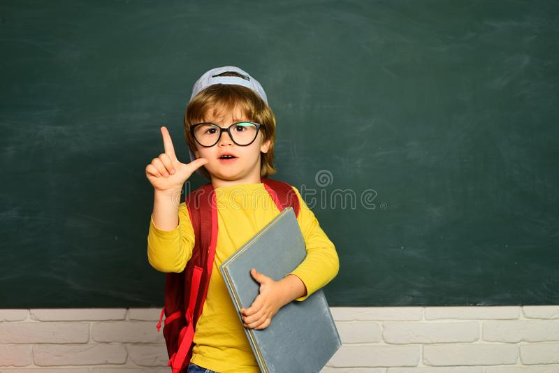 Cute little preschool kid boy in a classroom. Private school. Ready for school. Educational process. Funny little boy. Pointing up on blackboard royalty free stock images
