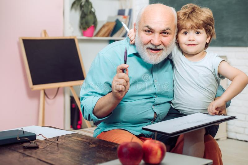 Cute little preschool kid boy with Grandfather in a classroom. Portrait of grandfather and grandson on blackboard in. Classroom stock photography