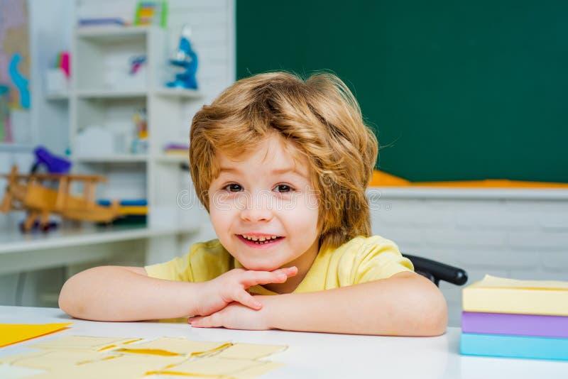 Cute little preschool kid boy with teacher study in a classroom. Cute little preschool kid boy with teacher study in a classroom stock photo