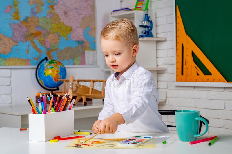 Cute little preschool kid boy with teacher study in a classroom. Elementary school and education. After school teaching. Cute little preschool kid boy with stock photo