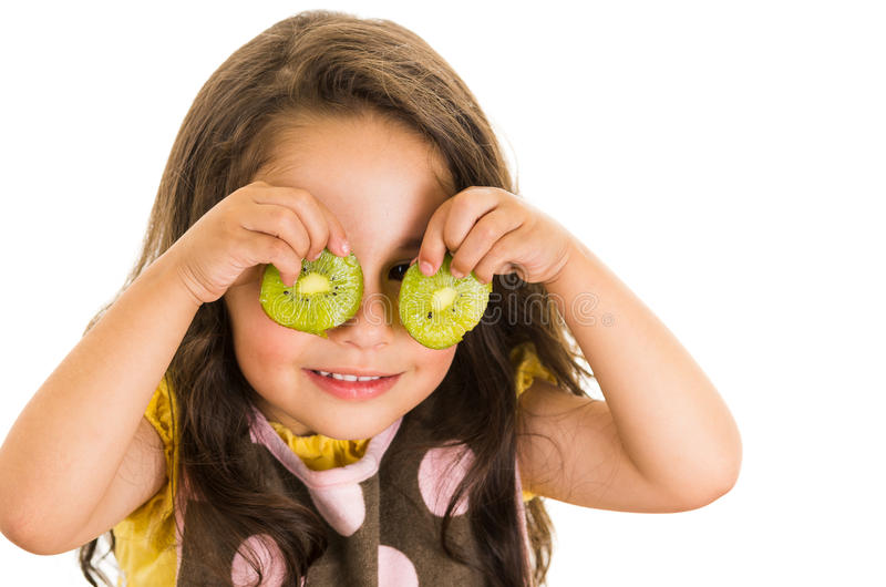 Cute little preschooler girl holding kiwi slices. In front of her eyes isolated on white royalty free stock photography