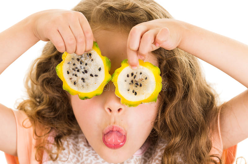 Cute little preschooler girl holding pitahaya. Slices in front of her eyes isolated on white royalty free stock photo