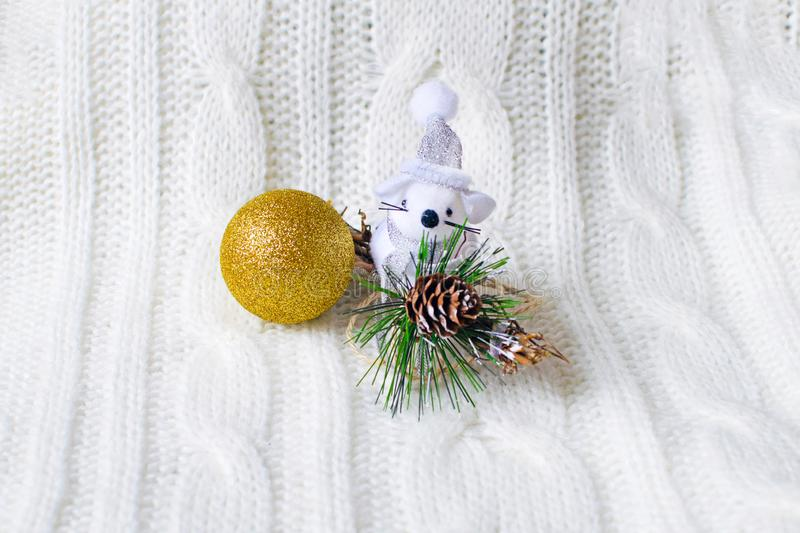 Cute little rat, mouse with christmas ball is sitting in a white knitted sweater. Present for New Year and Christmas. stock photography