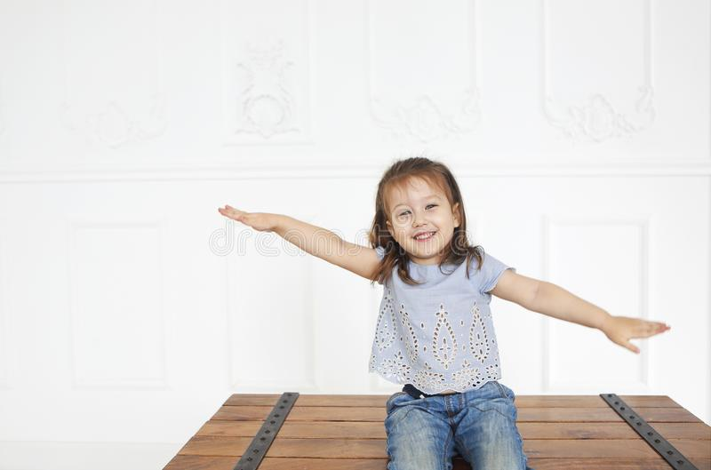 Cute little redhaired girl with blue eyes in denim jeans and blue shirt in a light room sitting on the cooffee table in loft style royalty free stock image