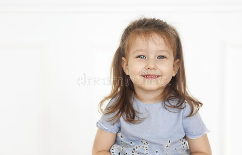 Cute little redhaired girl in denim jeans and blue shirt in a light room stock photos