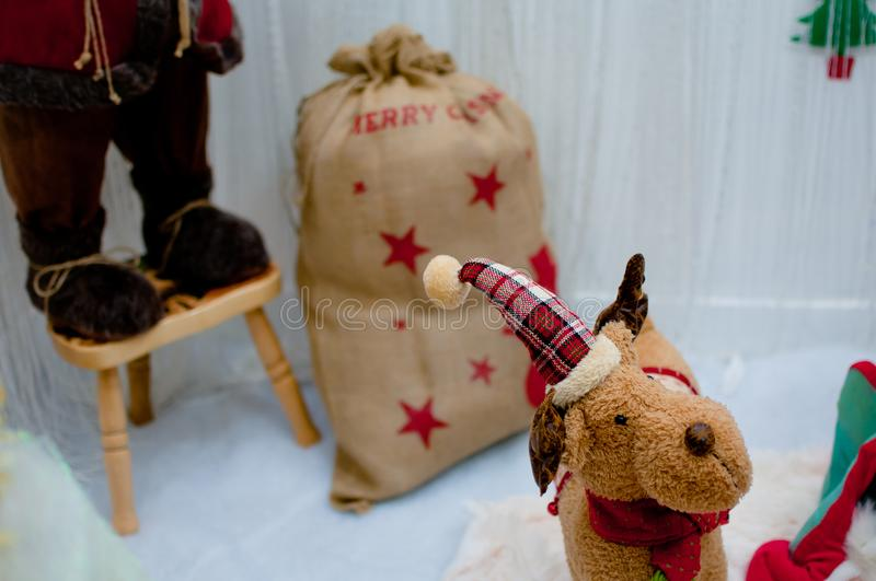 Cute little reindeer santa with hat. Christmas decoration with bag full of gifts stock photo