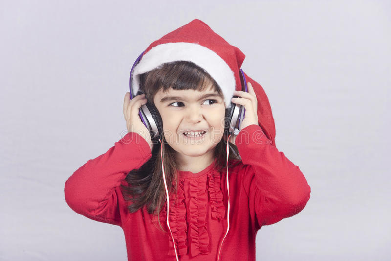 Cute little Santa girl listening to music stock image