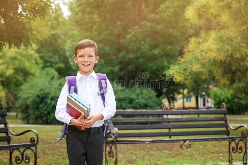 Cute little school child with stationery. In park royalty free stock photo