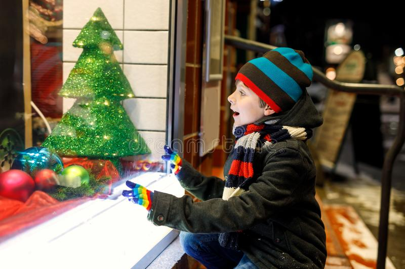 Cute little school kid boy on Christmas market. Funny happy child in fashion winter clothes making window shopping stock photo