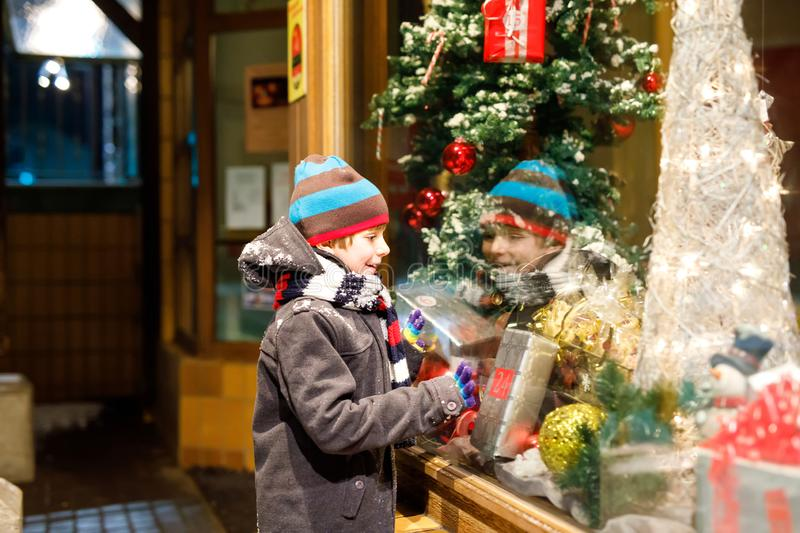 Funny happy child in fashion winter clothes making window shopping decorated with gifts, xmas tree stock images