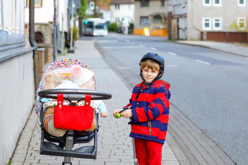 Cute little school kid boy riding on push scooter on the way to or from school. Schoolboy with cute little baby sister. On stroller or carriage pram. Happy stock images