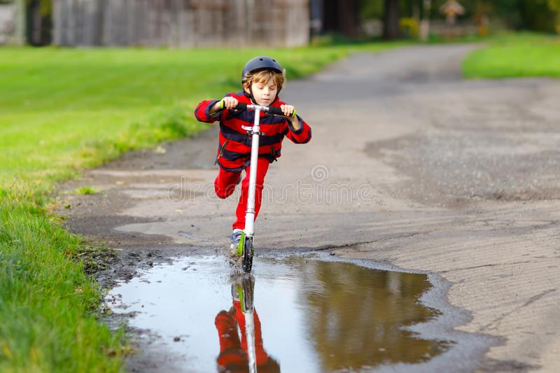 Cute little school kid boy riding on push scooter on the way to or from school. Schoolboy of 7 years driving through. Rain puddle. funny happy child in colorful stock photography