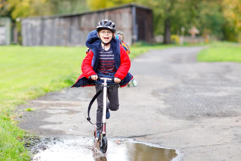 Cute little school kid boy riding on push scooter on the way to or from school. Schoolboy of 7 years driving through. Rain puddle. funny happy child in colorful royalty free stock photo