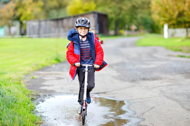 Cute little school kid boy riding on push scooter on the way to or from school. Schoolboy of 7 years driving through. Rain puddle. funny happy child in colorful royalty free stock photos