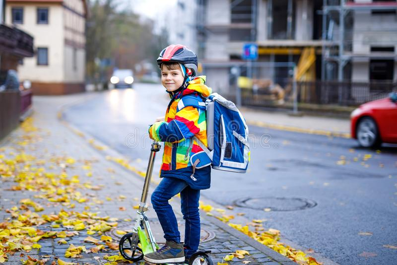 Cute little kid boy riding on scooter on way to school. Cute little school kid boy riding on scooter on way to elementary school. Child with safety helmet stock photo