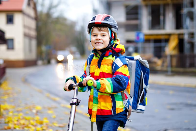 Cute little school kid boy riding on scooter on way to elementary school. Child with safety helmet, school bag on rainy. Autumn day. Traffic in the city and royalty free stock photo