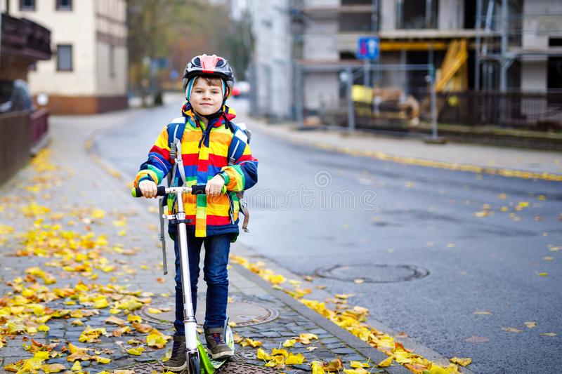 Cute little school kid boy riding on scooter on way to elementary school. Child with safety helmet, school bag on rainy. Autumn day. Traffic in the city and royalty free stock photography
