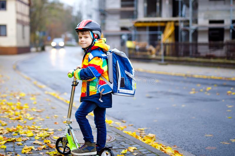 Cute little school kid boy riding on scooter on way to elementary school. Child with safety helmet, school bag on rainy. Autumn day. Traffic in the city and stock photography