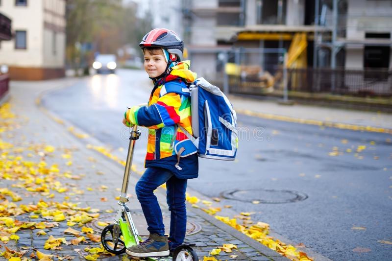 Cute little school kid boy riding on scooter on way to elementary school. Child with safety helmet, school bag on rainy. Autumn day. Traffic in the city and royalty free stock image