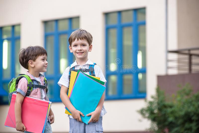 Cute little school students briskly talk on the schoolyard. Chil. Dren have a good mood. Warm spring morning. Behind shoulders at schoolmates schoolbags. In stock images