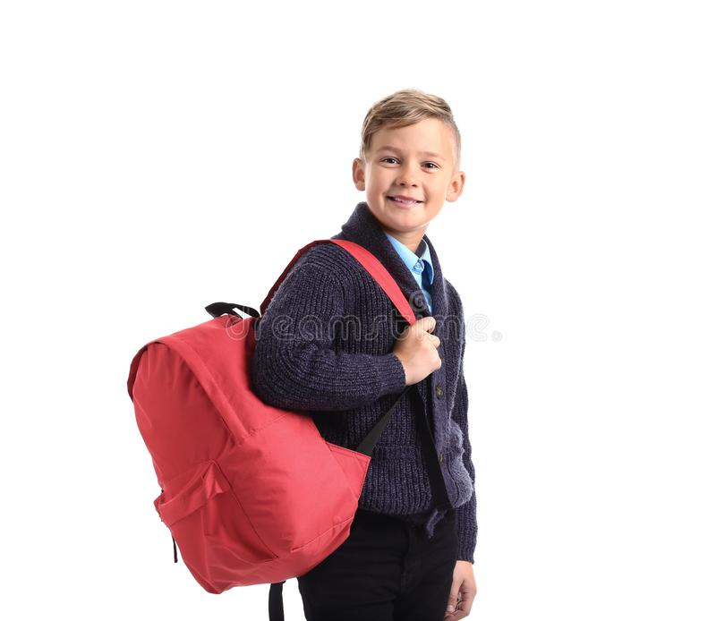 Cute little schoolboy with backpack on white background stock image