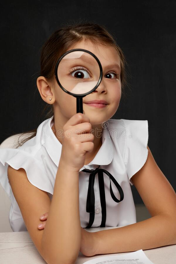 Free Cute Little Schoolgirl Looking Through Magnifying Glass Royalty Free Stock Photos - 217293358