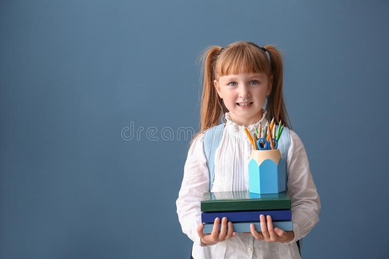 Cute little schoolgirl with stationery on color background stock photo