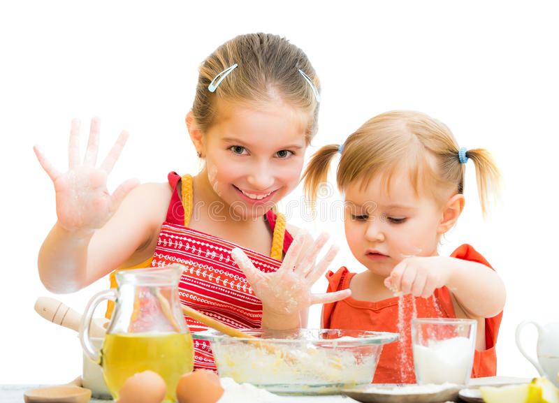 Cute little sisters baking on kitchen royalty free stock photography