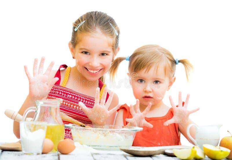 Cute little sisters baking on kitchen stock photo