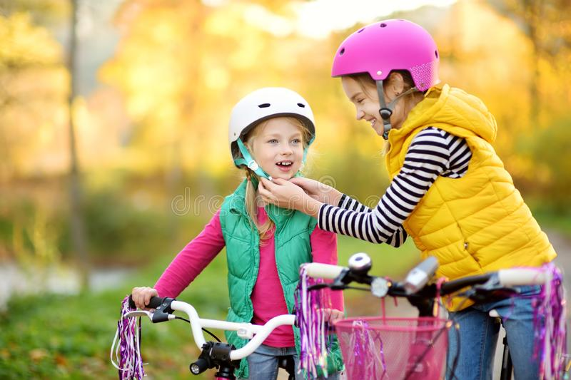 Cute little sisters riding bikes in a city park on sunny autumn day. Active family leisure with kids stock photography