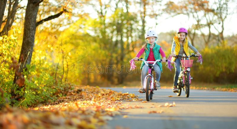 Cute little sisters riding bikes in a city park on sunny autumn day. Active family leisure with kids royalty free stock images