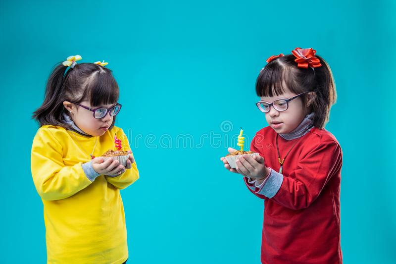 Cute little sisters wearing colorful outfits and carrying cupcakes royalty free stock images