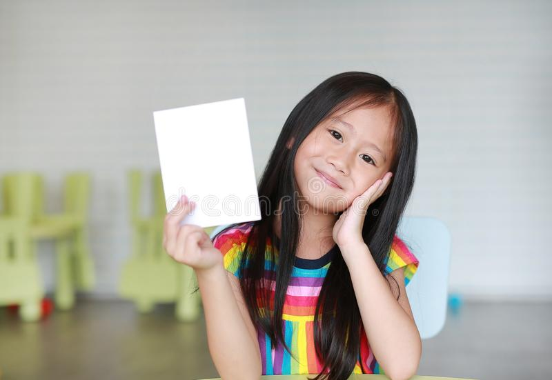 Cute little smiling Asian child girl holding blank white paper card in her hand. Kid showing empty paper note copy space in stock photos