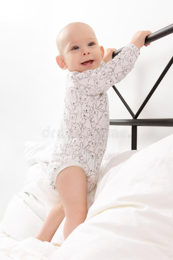 Cute little smiling baby boy infant standing on parent`s bed, holding onto the headboard. First attempts to stand up. stock photos