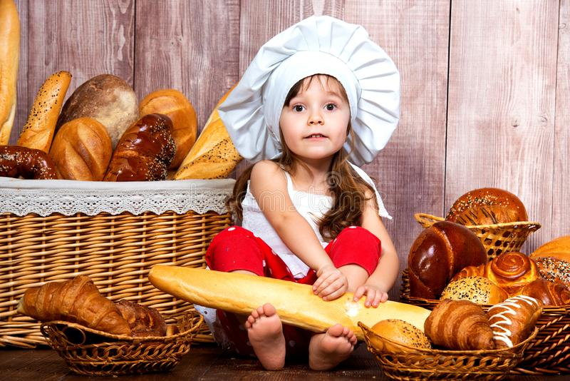 Cute little smiling girl in a chef`s cap sitting with a baguette in her hands near the wicker basket with bread rolls and bakery stock photography